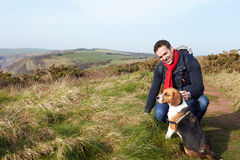 Man With Dog Walking Along Coastal Path Stock Photos