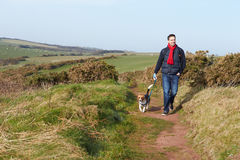 Man With Dog Walking Along Coastal Path Stock Photo