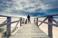 Man with dog in wild beach at storm.  stock photos