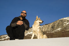 Man with dog in winter forest. Man and his Czechoslovakian wolf dog Royalty Free Stock Images