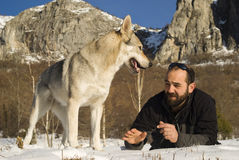 Man with dog in winter forest. Man and his Czechoslovakian wolf dog Stock Image