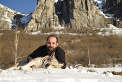 Man with dog in winter forest. Man and his Czechoslovakian wolf dog Royalty Free Stock Photography