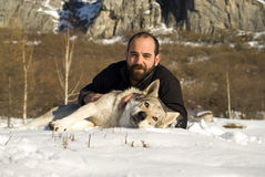 Man with dog in winter forest. Man and his Czechoslovakian wolf dog Royalty Free Stock Photo