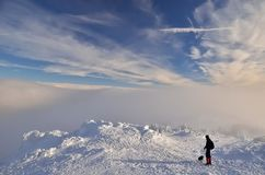 Man with dog in mountains over clouds. Man with dog on snowy trail with clouds at the background stock photo