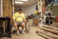 A man with is dog in a workshop, Mississippi. A man sat on a chair petting his dog in his workshop, Mississippi Royalty Free Stock Image