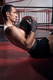 Man doing abdominal crunches with ball. Achieving results. Portrait of young handsome man doing abdominal crunches by using special fitness ball Royalty Free Stock Photos