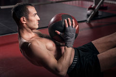Man doing abdominal crunches with ball. Intense workout. Young brawny man doing some abdominal crunches on floor with help of special fitness ball Stock Image