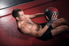 Man doing abdominal crunches with ball. Top view of young brawny man lying on floor and doing some exercises with special fitness ball Royalty Free Stock Image