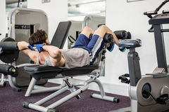 Man doing abdominal crunches on bench Stock Images