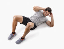 Man doing abdominals. Athletic man doing abdominals, isolated over a white background Royalty Free Stock Photography
