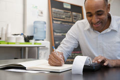 Man doing accounts in cafe Royalty Free Stock Photos