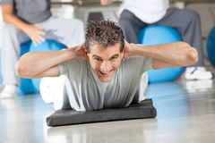 Man doing back exercises in fitness. Happy man doing back exercises on gym mat in fitness center Stock Image