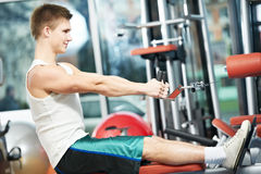 Man doing back exercises at fitness gym. Fitness man doing back muscles exercises with training weight machine station in gym Stock Photo