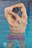 Man doing back training in aqua. Man with muscles doing back training in aqua fitness swimming pool Royalty Free Stock Photo