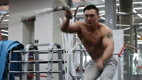 Man doing battling rope exercise at the gym. Young athlete doing exercise with ropes stock footage