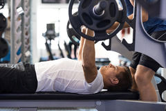 Man doing bench press. Determined young men lifting barbell. Latin men doing barbell bench press in gym with personal trainer. Man in gym exercising with barbell royalty free stock photos