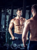 Man doing bicep curls. Young adult man doing bicep curls in modern gym Royalty Free Stock Image