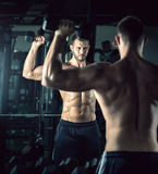 Man doing bicep curls. Young adult man doing bicep curls in modern gym Stock Photos