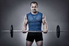 Man doing biceps curl with barbell Stock Photos