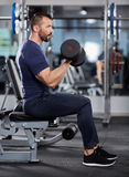 Man doing biceps curl seated Stock Image