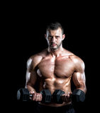 Man doing biceps curls in gym. Young adult man doing barbell press in gym. Black background. Gym training workout Royalty Free Stock Images