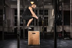 Man Doing A Box Jump Exercise. Young Athlete Man Doing A Box Jump Exercise In The Gym royalty free stock photo
