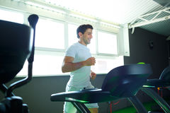 Man doing cardio training program in fitness center. Athletic man doing cardio training program in fitness center Royalty Free Stock Photo