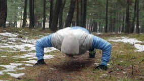 Man doing clapping push ups outside in forest. Crossfit traing outdoors stock footage
