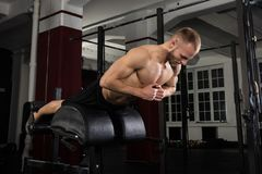 Man Doing Core Exercise On Exercise Equipment. Low Angle View Of A Man Doing Core Exercise On Exercise Equipment In The Gym Royalty Free Stock Image