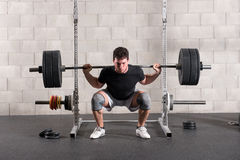 Man doing a crossfit back squat exercise. Raising a barbell weight onto his shoulders while squatting before standing upright stock images