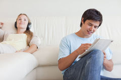 Man doing crosswords while his fiance is listening to music Royalty Free Stock Images