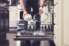 Man doing dishes cleaning in the kitchen household chores. Father dad husband doing household chores washing dishes in kitchen stock image