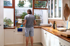Man doing the dishes Stock Images