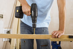 Man doing DIY at home, drilling hole in piece of timber on workbench, front view, mid-section Stock Images
