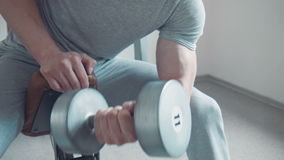 Man doing dumbbell concentration curl. Close-up of unrecognizable sportsman doing dumbbell concentration curl stock footage