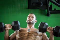 Man doing dumbbell press while lying down Stock Photo