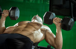 Man doing dumbbell press while lying down Royalty Free Stock Image