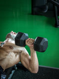 Man doing dumbbell press while lying down Stock Photos
