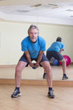 Man doing dumbbell swings Stock Image