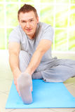 Man doing exercise. Portrait cheerful man doing stretching exercise sitting on blue mat, at the home gym Stock Photo