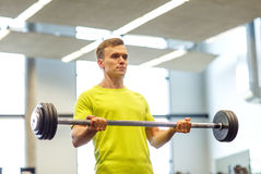 Man doing exercise with barbell in gym Stock Images