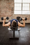 Man doing exercise with dumbbells while lying on bench Stock Photo
