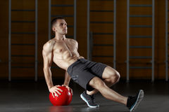 Man doing exercise for muscles of back with fitness ball. Handsome and muscular man doing sport exercise on abdominal muscles, legs, hands and muscles of the Royalty Free Stock Images
