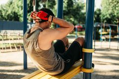 Man doing exercise on press outdoor, back view royalty free stock image