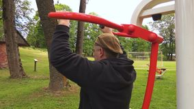 Man doing exercise for shoulders on training machine. In summer day stock video footage