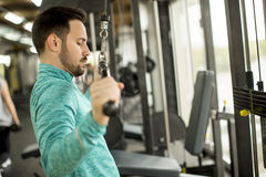 Man doing exercise for triceps in the gym on mashine Stock Images