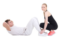 Man doing exercises for abdominal muscles with his girlfriend is Royalty Free Stock Photos