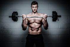Man doing exercises with barbell in The Gym's Studio Royalty Free Stock Photography