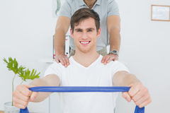 Man doing exercises with the help of therapist in office Royalty Free Stock Photo