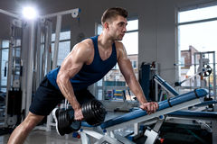 Man doing exercises with one dumbbell in the gym. Young muscular man in a vest doing one-arm dumbbell rows on bench in gym Stock Images